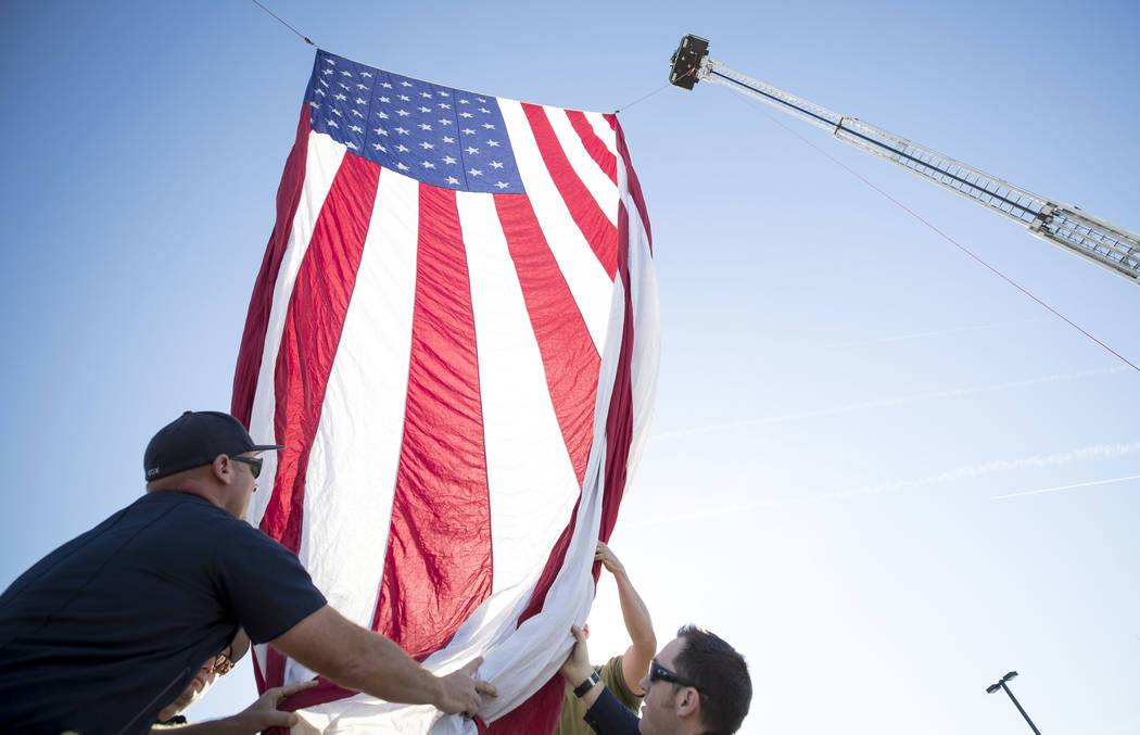Clark County Firefighters hang an American Flag from the ladders of two firetrucks ahead of the Project Hero Honor Ride in Las Vegas, Saturday, Nov. 11, 2017. Over 700 riders participated in the n ...