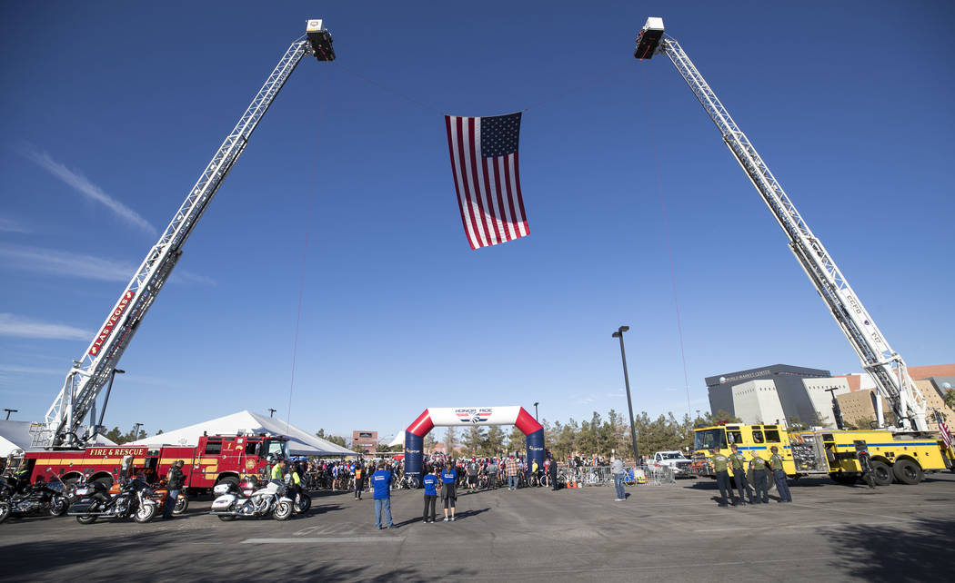 An American flag anchored by the ladders of two firetrucks spans the staring line of the Project Hero Honor Ride in Las Vegas, Saturday, Nov. 11, 2017. Over 700 riders participated in the non-comp ...