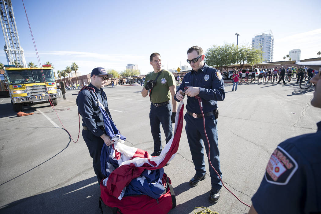 Clark County Firefighters Zack Schaffer, from left, Parker Simper and Matt Turner prepare to hang an American Flag from the ladders of two firetrucks ahead of the Project Hero Honor Ride in Las Ve ...