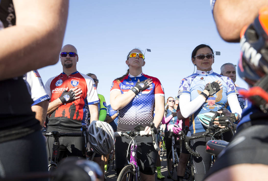 Participating cyclists stand for the national anthem before the start of the Project Hero Honor Ride in Las Vegas, Saturday, Nov. 11, 2017. Over 700 riders participated in the non-competitive race ...