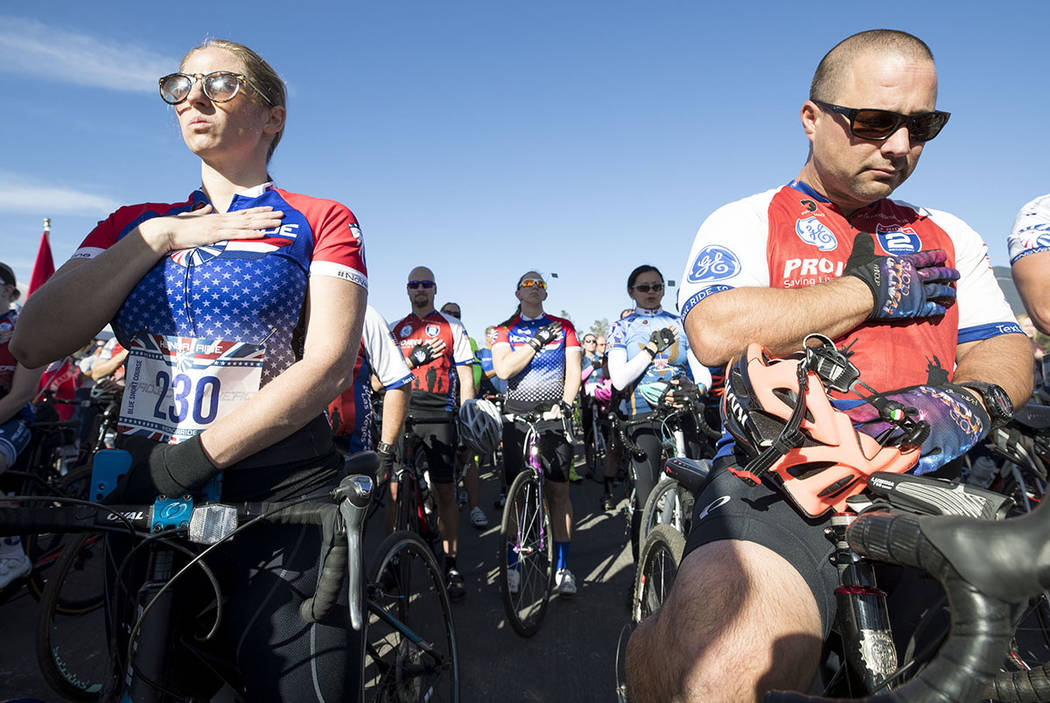 Cyclists Shauntele Harless, left, and Max Caravajal stand for the national anthem ahead of the Project Hero Honor Ride in Las Vegas, Saturday, Nov. 11, 2017. Over 700 riders participated in the no ...