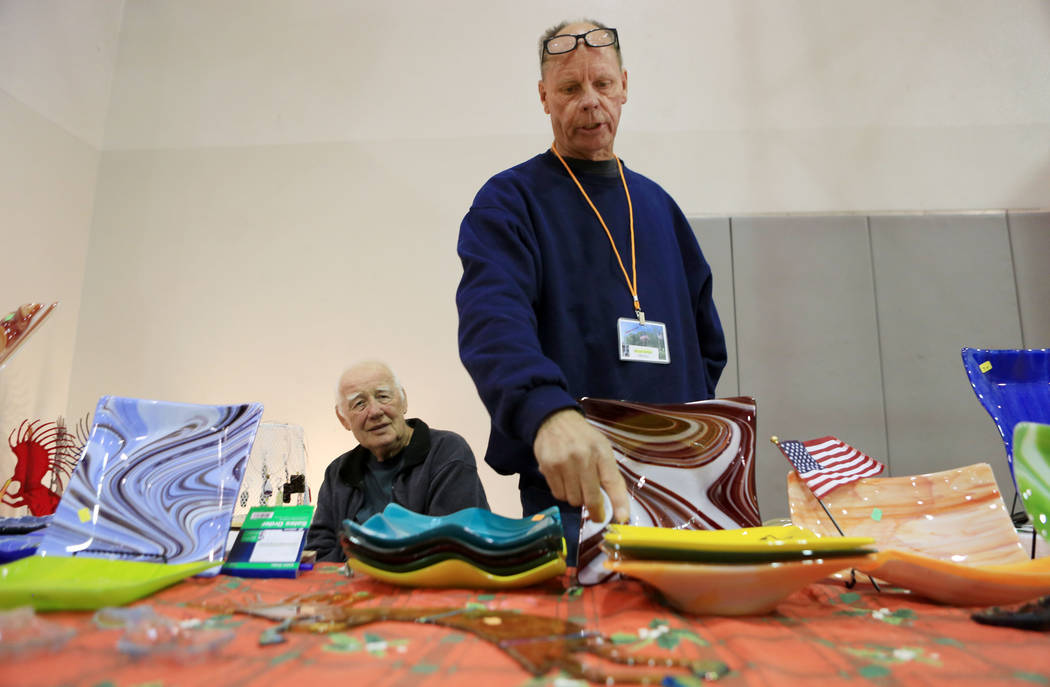 Artist based in Pahrump, Bryan Myers, right, shows off his pieces with Gene Nielsen at their booth during the Winter Art Festival in the Boulder City Parks and Recreation gym in Boulder City, Sund ...