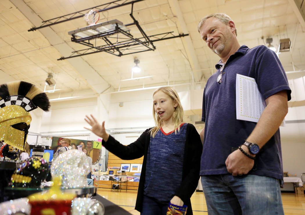 Lyndsey Haff, 11 and her father Kevin Haff admire Black Raven crystal art designs by Dana Notario during the Winter Art Festival in the Boulder City Parks and Recreation gym in Boulder City, Sunda ...