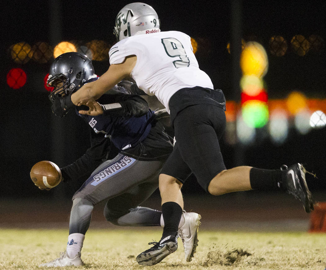 Green Valley's Mitch Jacobs (9) sacks Canyon Springs' quarterback Kayjon Edwards (8) in the playoff football game at Canyon Springs High School in Las Vegas, Thursday, Nov. 9, 2017. Green Valley w ...