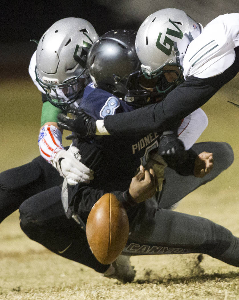 Canyon Springs' quarterback Kayjon Edwards (8) is tackled by Green Valley players in the playoff football game at Canyon Springs High School in Las Vegas, Thursday, Nov. 9, 2017. Green Valley won  ...