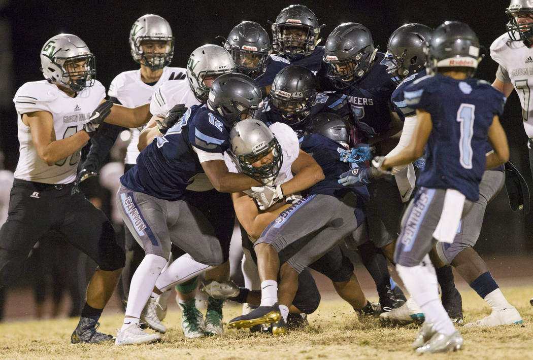 Green Valley's Noah Hawthorne (22) is tackled against Canyon Springs in the playoff football game at Canyon Springs High School in Las Vegas, Thursday, Nov. 9, 2017. Green Valley won 14-7. Erik Ve ...