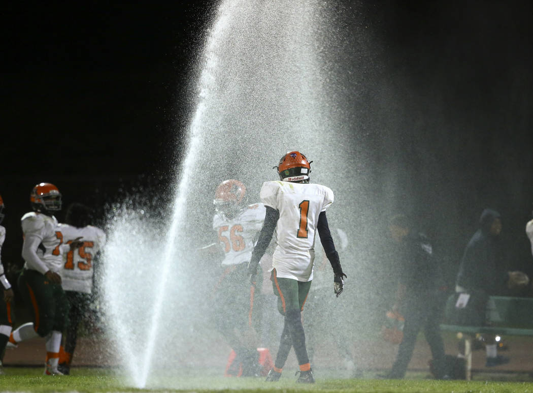 Mojave players walk in the water after sprinklers went off during the Class 3A state quarterfinal game at Virgin Valley High School in Mesquite on Thursday, Nov. 9, 2017. Chase Stevens Las Vegas R ...