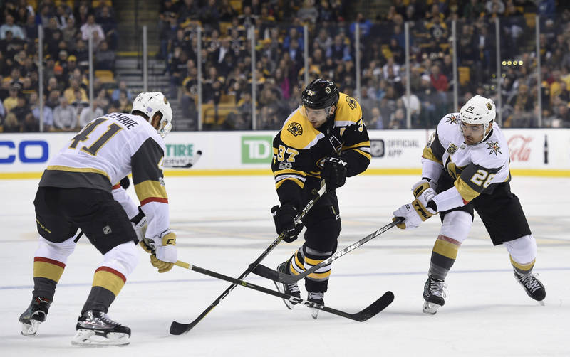 Nov 2, 2017; Boston, MA, USA; Boston Bruins center Patrice Bergeron (37) controls the puck between Vegas Golden Knights left wing Pierre-Edouard Bellemare (41) and left wing William Carrier (28) d ...