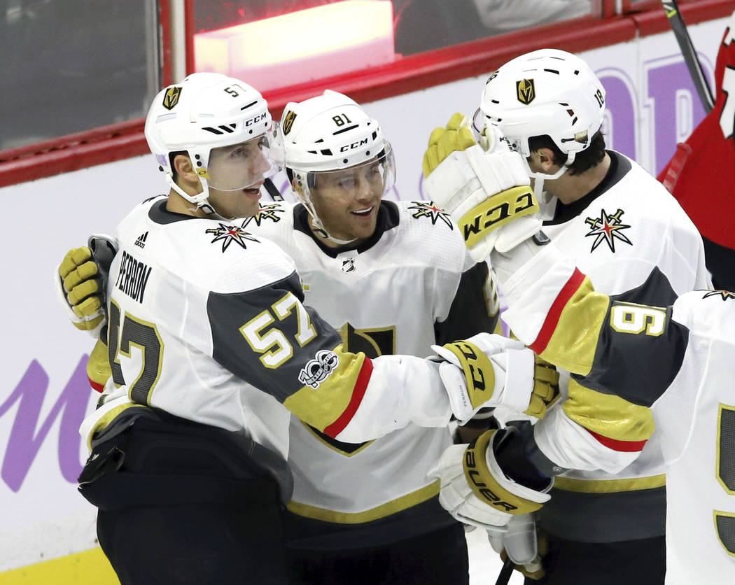 Vegas Golden Knights center Jonathan Marchessault (81) celebrates his goal with left wing David Perron (57) and left wing James Neal (obscured) during the second period of an NHL hockey game again ...