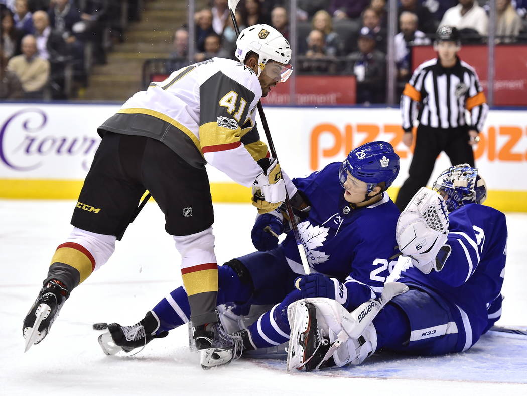 Vegas Golden Knights left wing Pierre-Edouard Bellemare (41) checks Toronto Maple Leafs center William Nylander (29) into goalie Frederik Andersen (31) during the first period of an NHL hockey gam ...