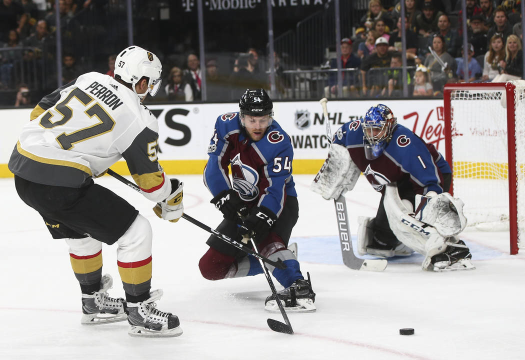 Golden Knights' David Perron (57) attempts to get the puck past Colorado Avalanche's Anton Lindholm (54) as Colorado Avalanche goalie Semyon Varlamov (1) defends during an NHL hockey game at T-Mob ...