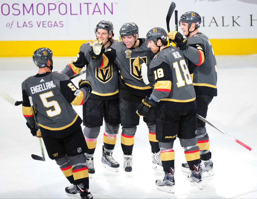 Vegas Golden Knights forward David Perron, center, high fives Deryk Engellandc (5) after Perron scored a goal against the Winnipeg Jets in the first period of their NHL hockey game at T-Mobile Are ...