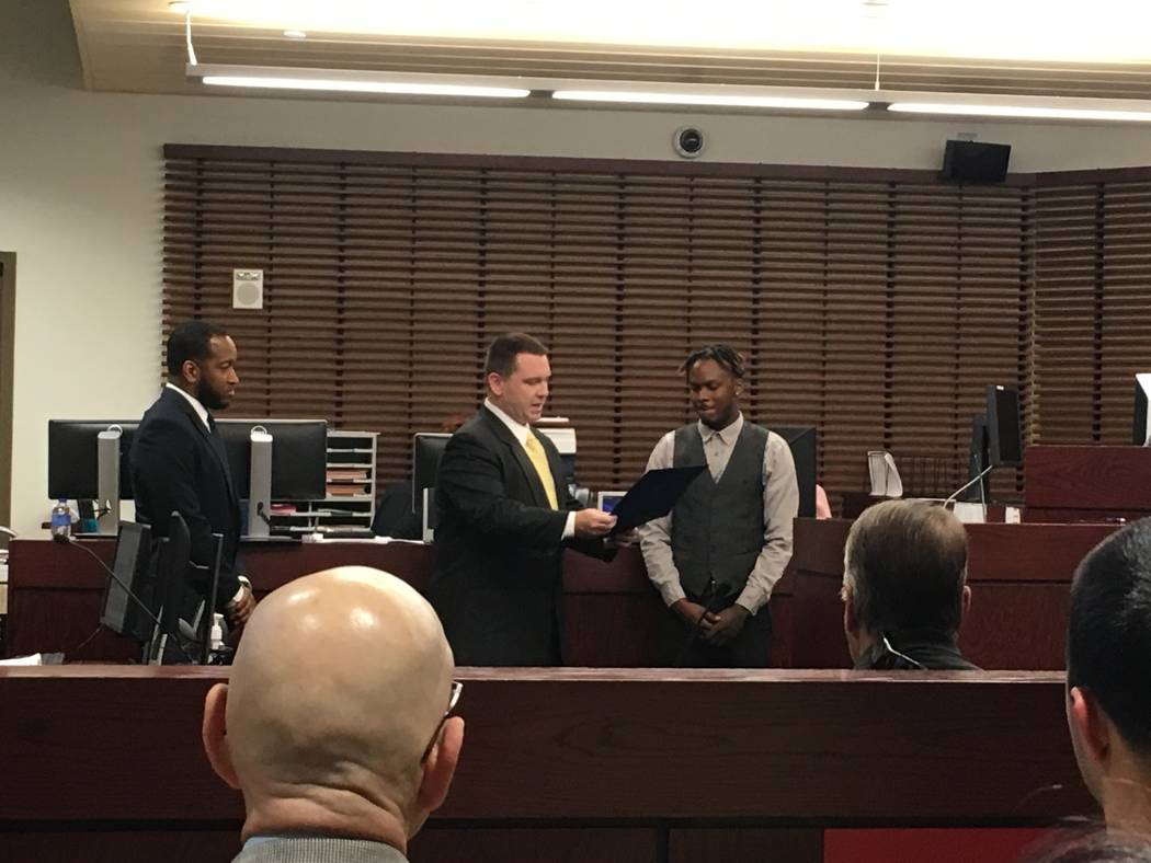 Mario Allen stands in front of the court as Blake Boles, a representative from Congresswoman Jacky Rosen's office, presents him with a certificate of congratulations on completing the course. (Die ...