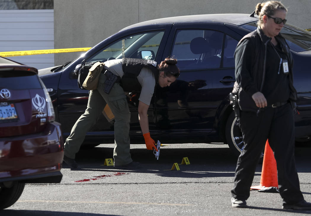 Crime scene investigators collect a gun as evidence at the scene of a shooting that occurred in an alley behind a 7-Eleven store near the intersection of East Sunset Road and South Eastern Avenue  ...