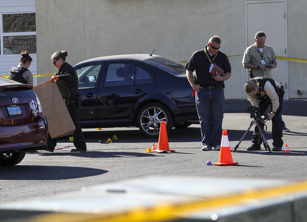 Crime scene investigators collect evidence at the scene of a shooting that occurred in an alley behind a 7-Eleven store near the intersection of East Sunset Road and South Eastern Avenue in Las Ve ...