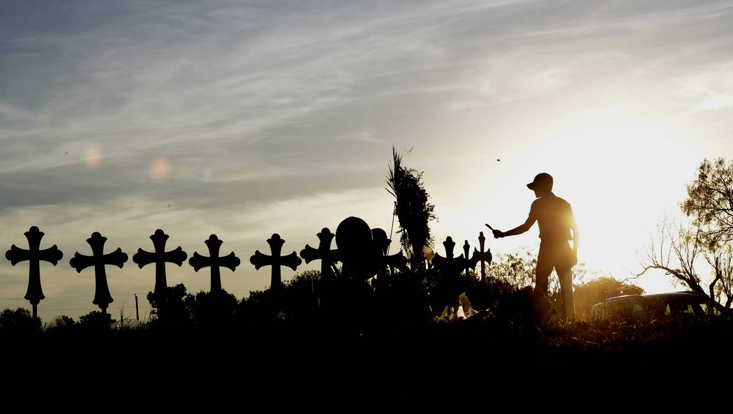 Derrick Bernoden burns sage at a makshift memorial for the First Baptist Church victims Tuesday, Nov. 7, 2017, in Sutherland Springs, Texas. A man opened fire inside the church in the small South  ...