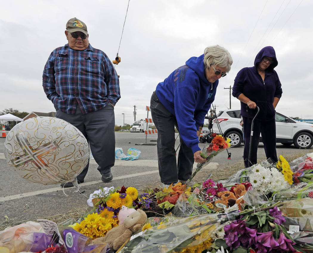 Barbara Solano, center, places flowers at a makeshift memorial for the victims of the First Baptist Church shooting Thursday, Nov. 9, 2017, in Sutherland Springs, Texas. A man opened fire inside t ...
