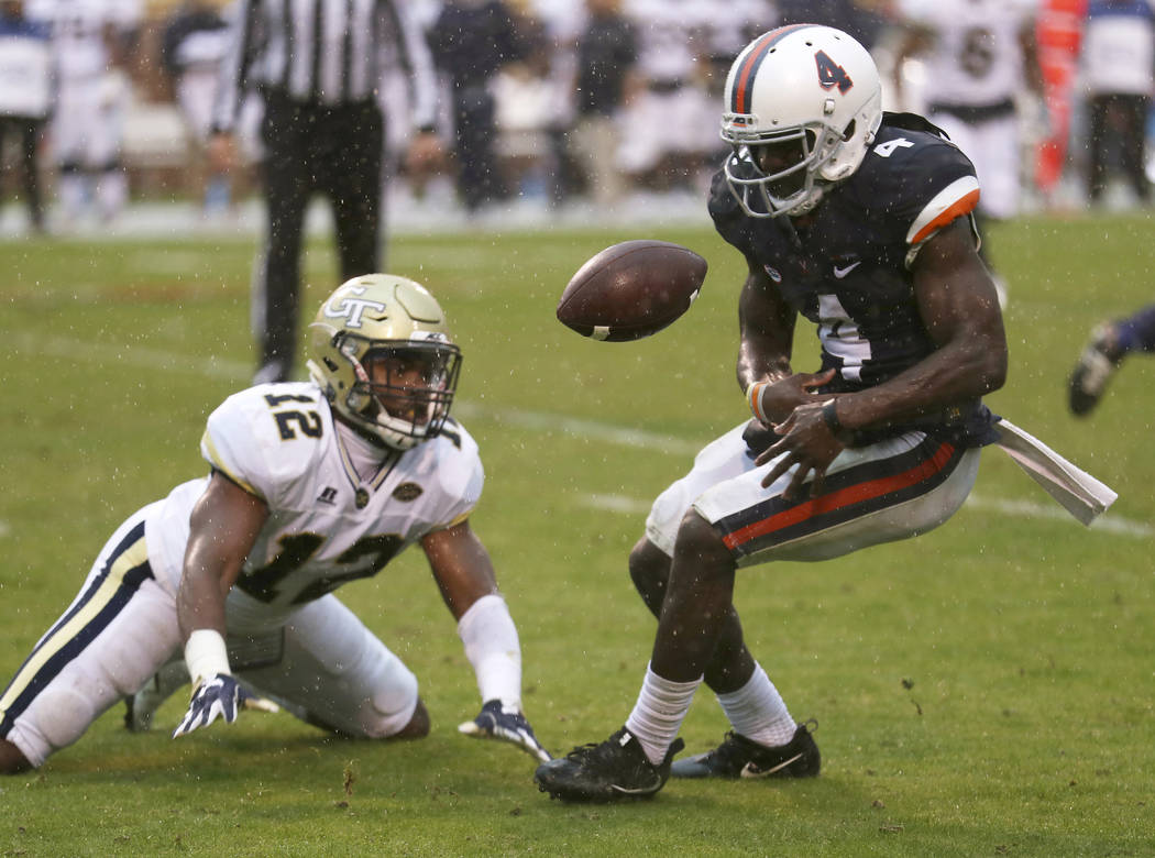 Virginia's Olamide Zaccheaus (4) fumbles the ball after a short reception during the first half of an NCAA college football game against Georgia Tech on Saturday, Nov. 4, 2017, in Charlottesville, ...