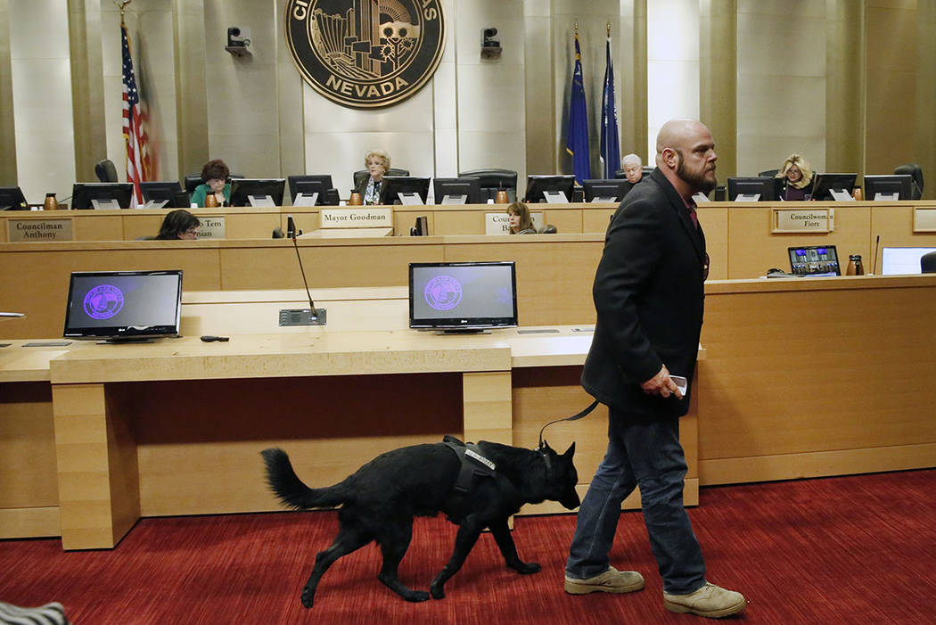 U.S. Army veteran, Michael Neil, accompanied by his service dog Yamas, leaves the podium after speaking during the City Council meeting at Las Vegas City Hall Wednesday, Nov. 15, 2017. Neil suppor ...