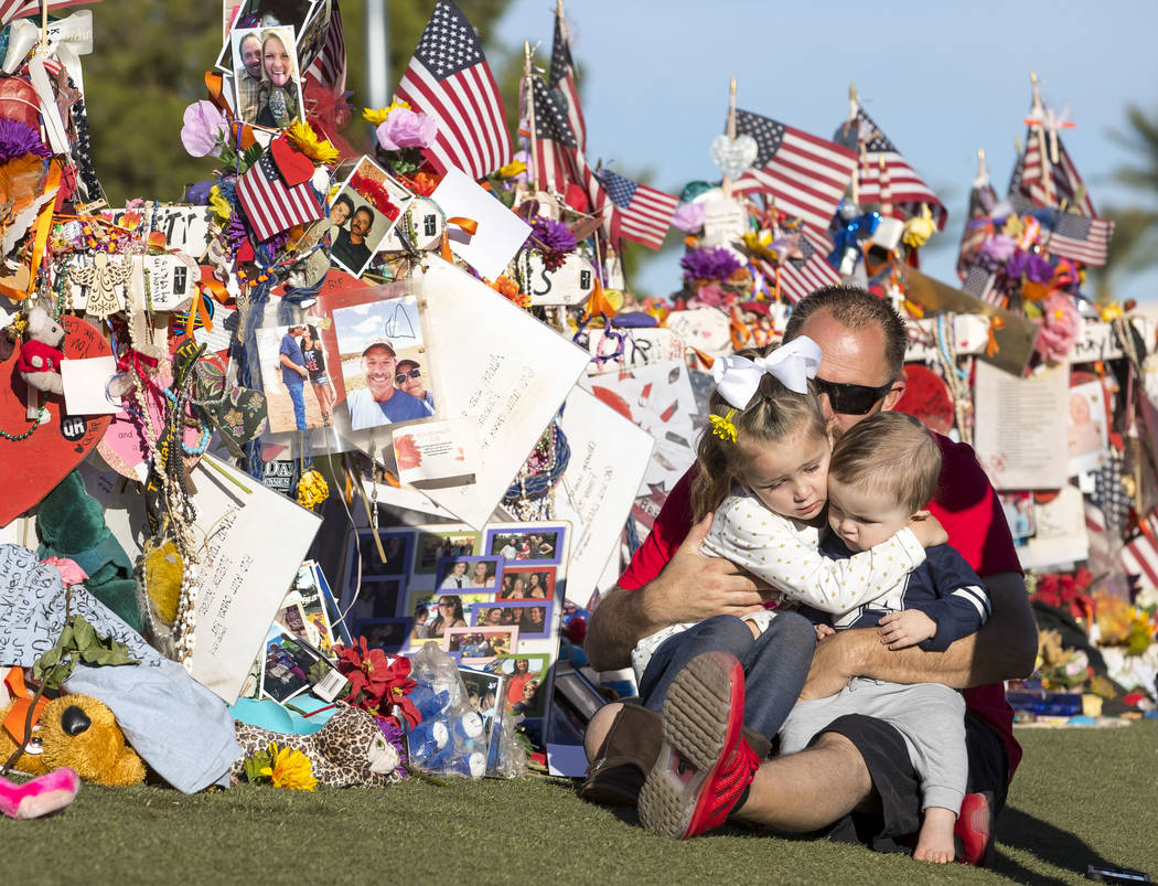 Shawn Schwanbeck, center, of Arizona, hugs his daughter Avri, 4, and nine-month-old son Austin as they visit the cross of his father, Brett Schwanbeck, at a memorial for the victims of the Route 9 ...