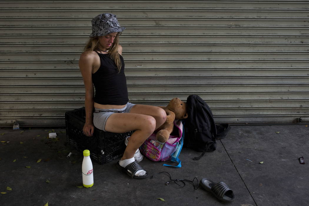 A young homeless woman, in a drug-induced state, wobbles while sitting on a milk case with a teddy bear in Los Angeles' Skid Row area, home to the nation's largest concentration of homeless people ...