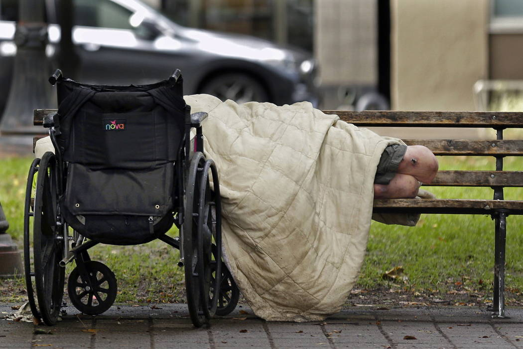 A person sleeps next to a wheelchair on a park bench in downtown Portland, Ore., not far from the city's trendy Pearl District, last month.  (AP Photo/Ted S. Warren)