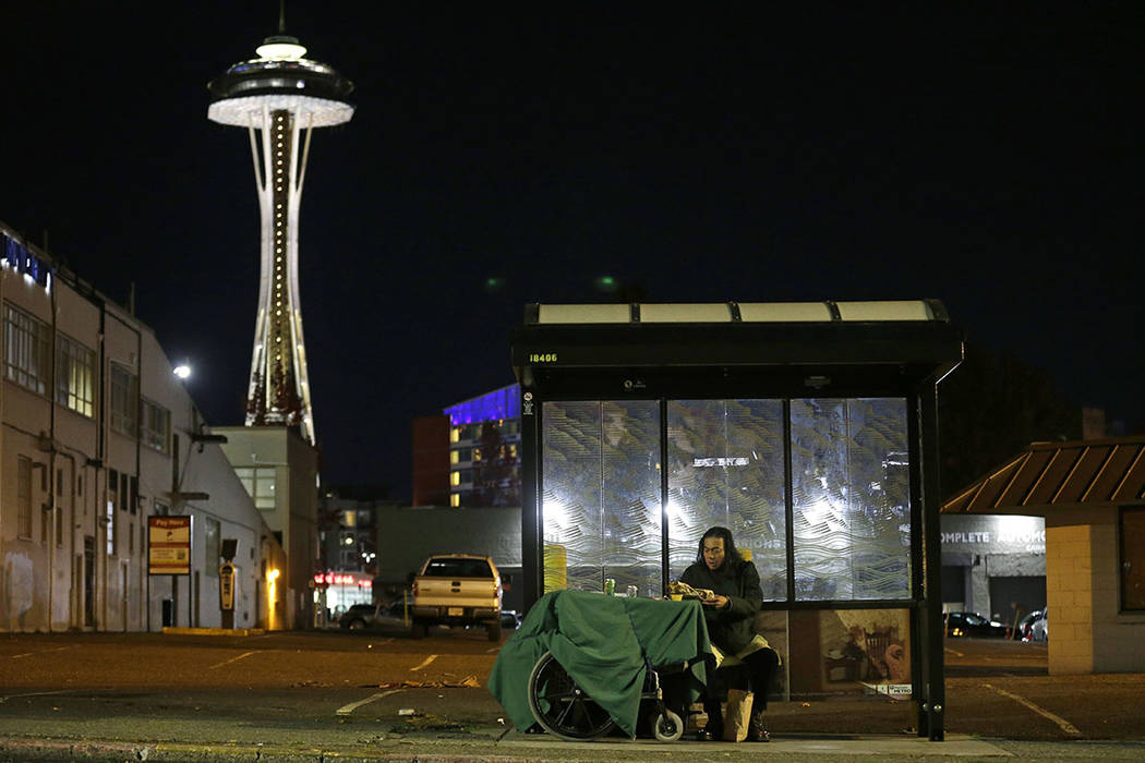 Dave Chung, who says he has been homeless for five years on the streets of California and Washington state, eats a meal before bedding down in a bus shelter in view of the Space Needle in Seattle  ...