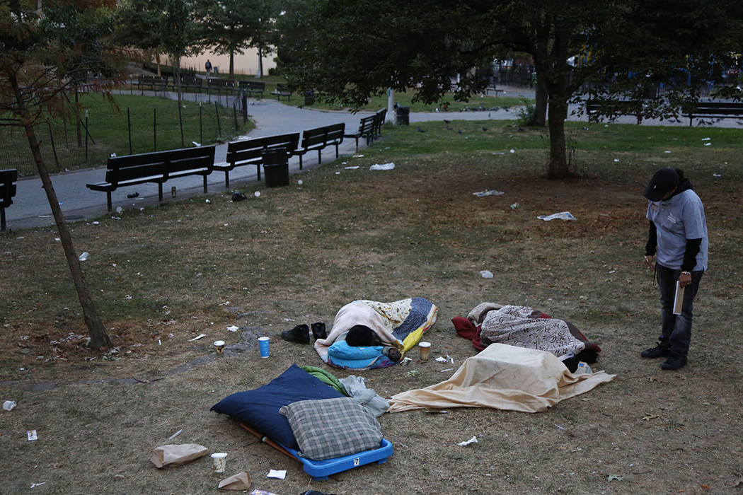 Center for Urban Community Services caseworker Gladys Rivera talks to some homeless people sleeping in a park in the Harlem section of New York last month. (AP Photo/Seth Wenig)