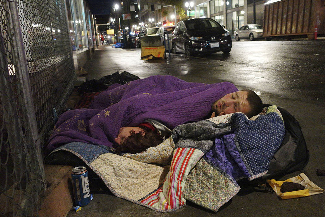 Taz Harrington, right, sleeps with his girlfriend, Melissa Ann Whitehead, on a street in downtown Portland, Ore., in September. (AP Photo/Ted S. Warren)