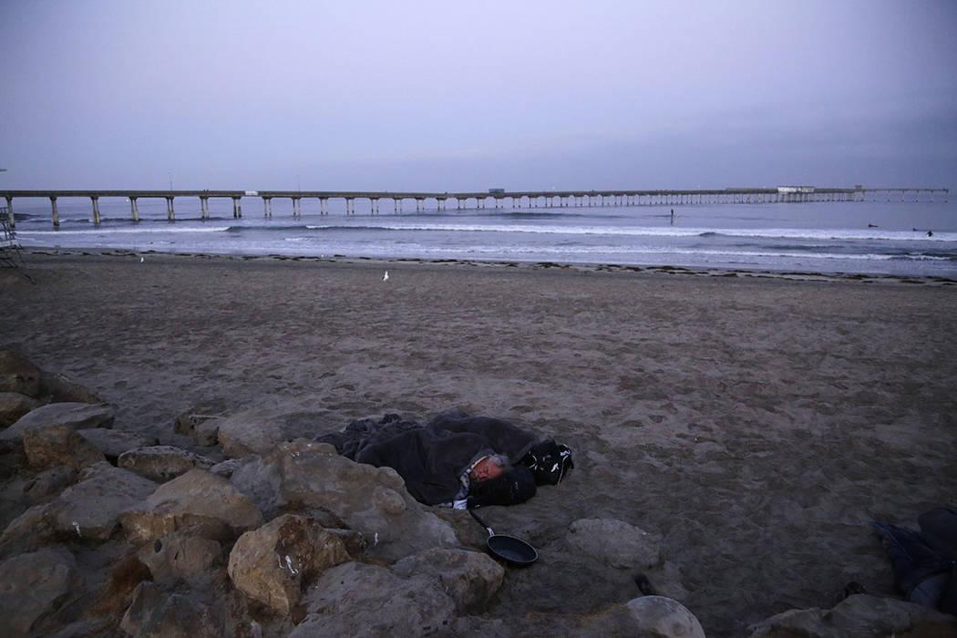 A person sleeps under a blanket on a beach near the Ocean Beach Pier in San Diego in September. (AP Photo/Gregory Bull)