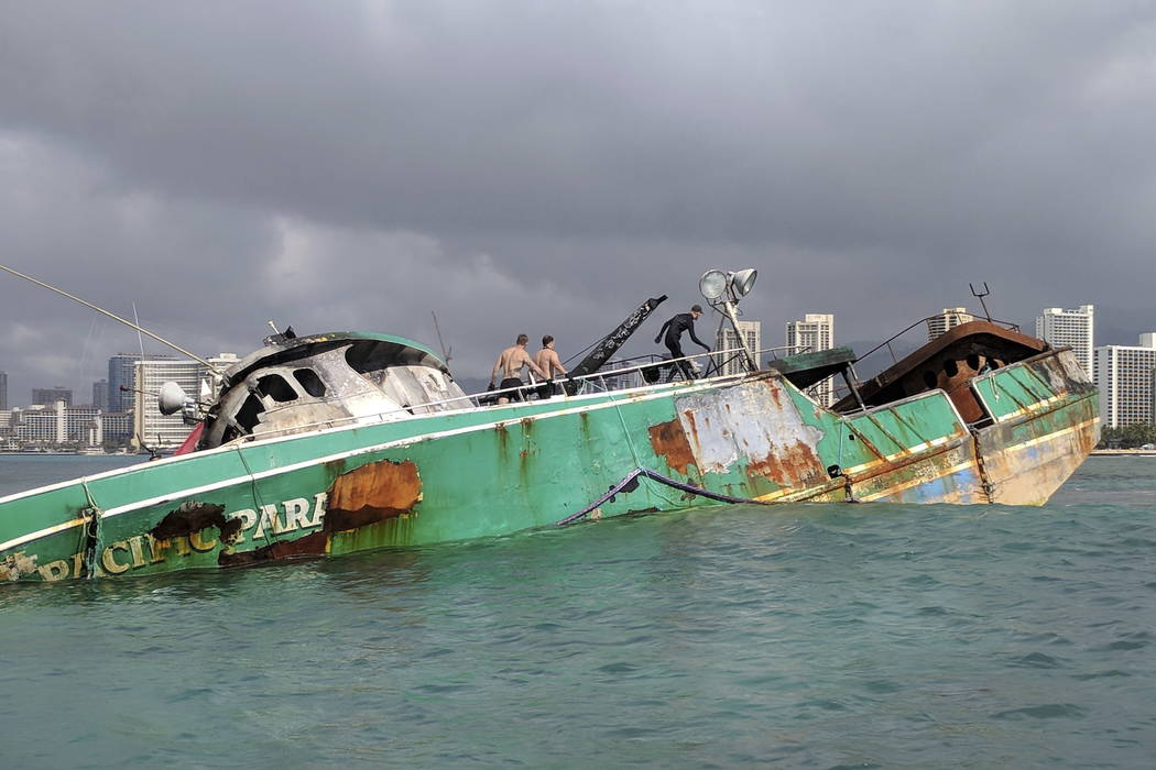 Responders continue work to salvage the commercial fishing vessel Pacific Paradise still grounded just off Kaimana Beach on Oahu, Hawaii. (Chief Petty Officer Sara Muir/U.S. Coast Guard via AP)