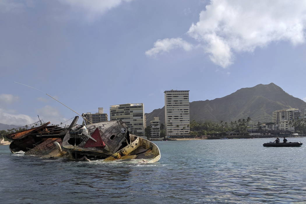 Responders continue work to salvage the commercial fishing vessel Pacific Paradise still grounded just off Kaimana Beach on Oahu, Hawaii. (U.S. Coast Guard via AP)