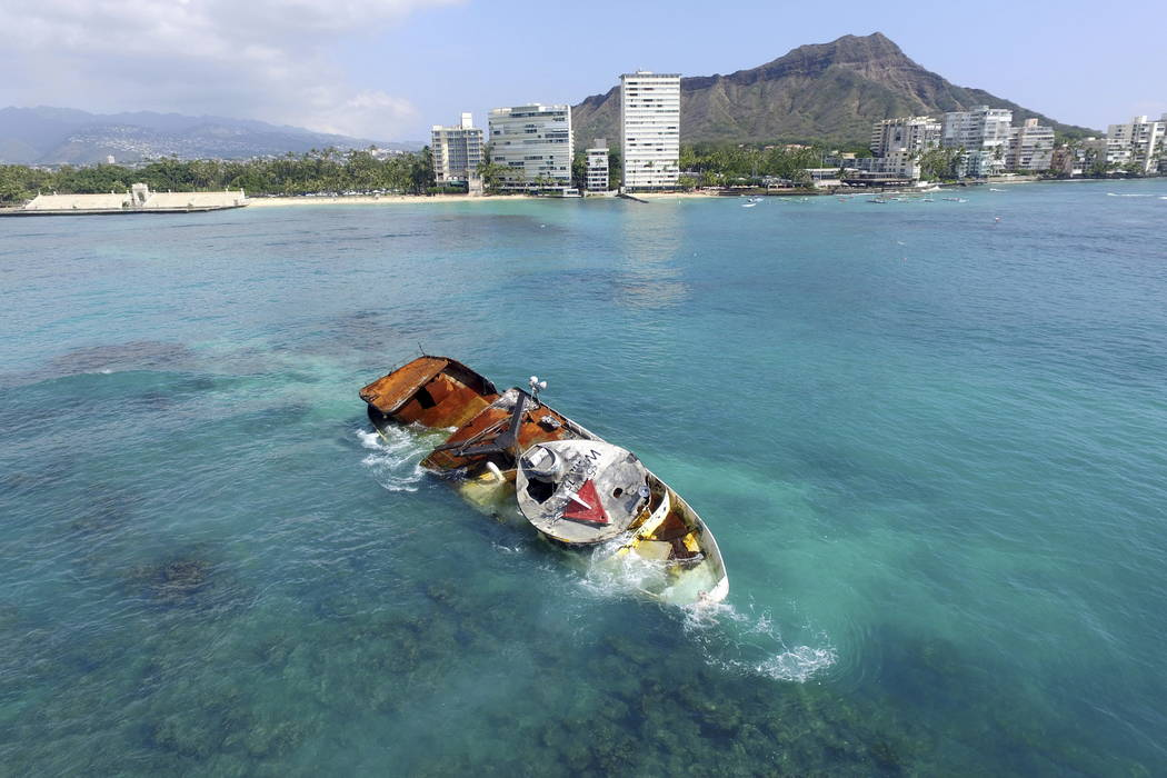 This drone photo shows the fishing boat Pacific Paradise, leaking oil and diesel fuel just offshore of hotels on Waikiki's pristine white sand beaches with Diamond Head in the background in Honolu ...