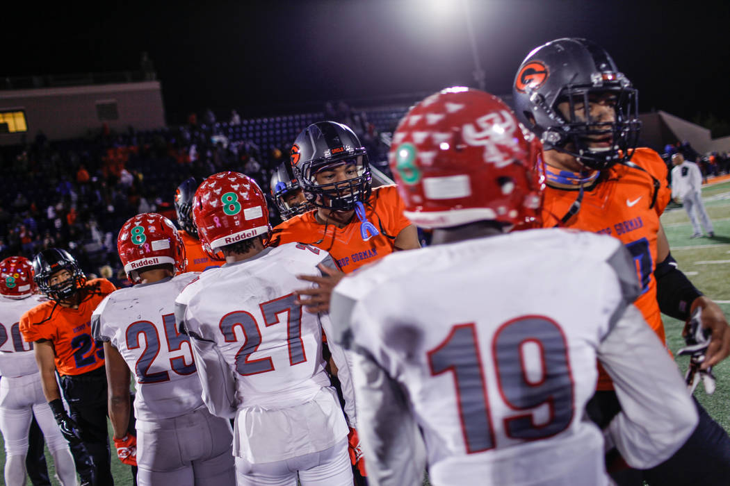 Bishop Gorman's Cedric Tillman (4), third from right, pats Arbor View's Niles Scafati Boyce (27), fourth from right, on the back at the end of the Class 4A Sunset Region Title football game at Bis ...