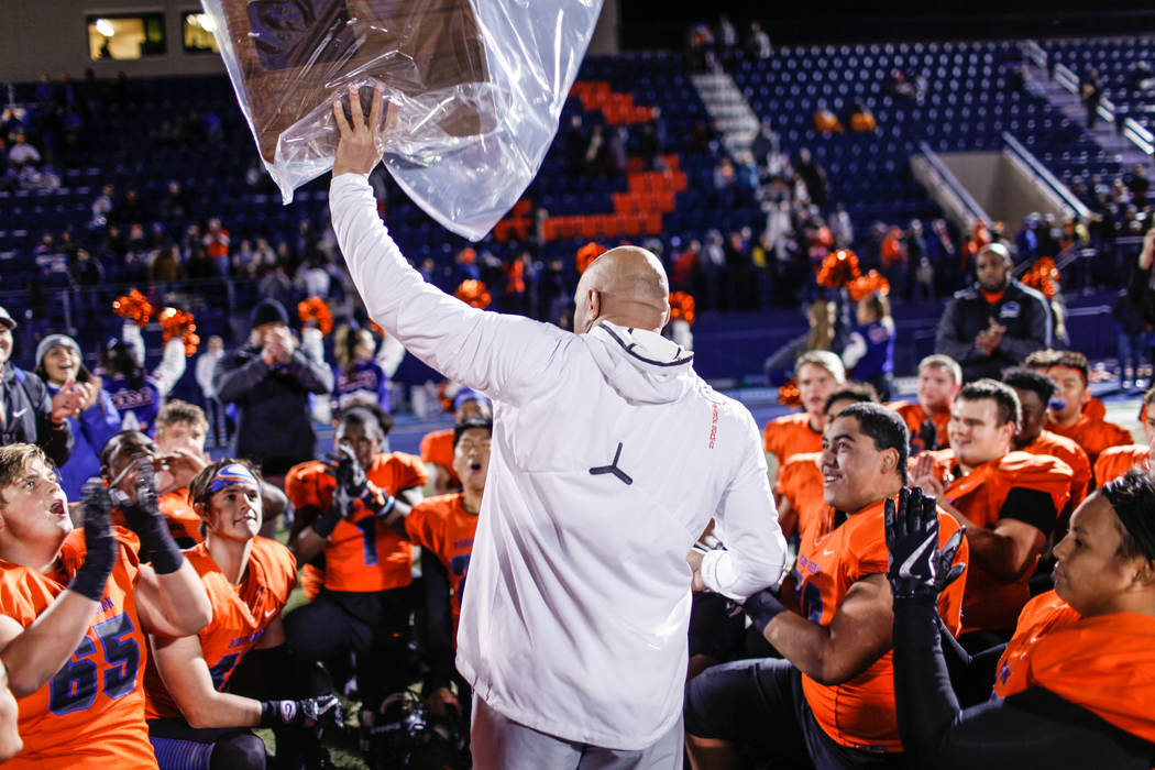 Bishop Gorman head coach Kenny Sanchez lifts a plaque as he celebrates with his team after defeating Arbor View 42-7 in the Class 4A Sunset Region Title football game at Bishop Gorman High School  ...