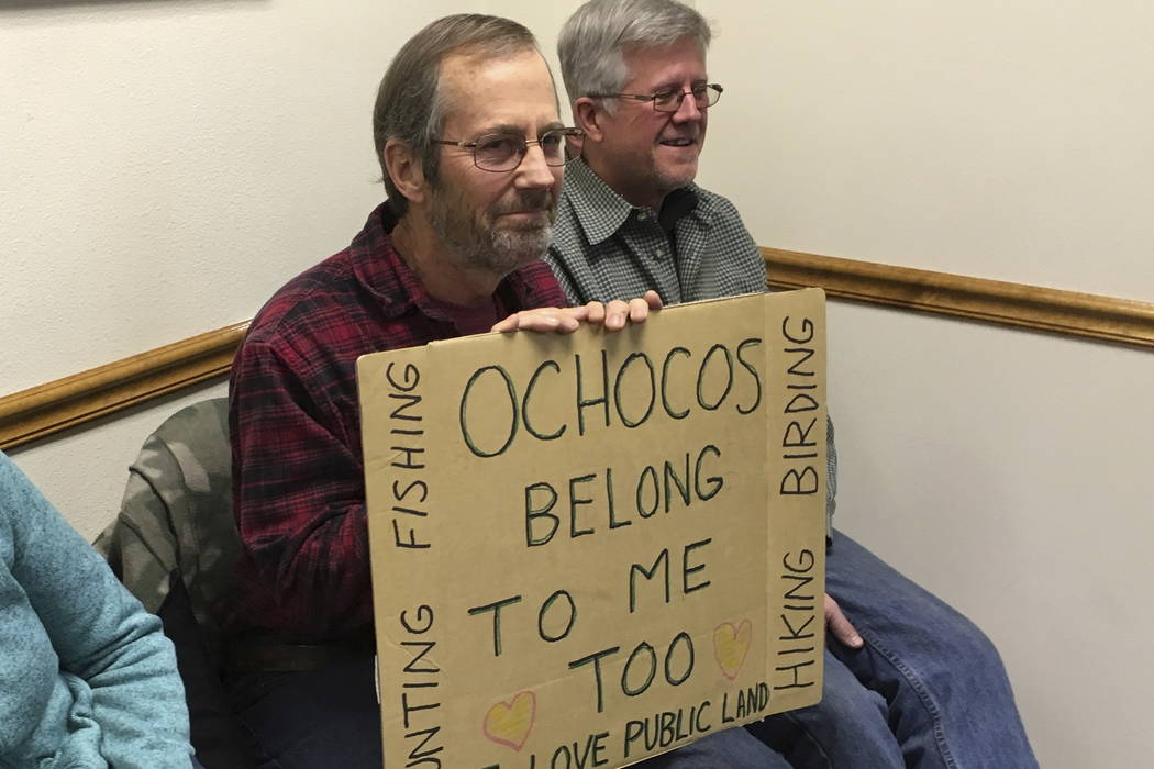 Chris Scranton holds a sign during the meeting of the Crook County commissioners on Wednesday, Nov. 8, 2017 in Prineville, Ore. (AP Photo/Andrew Selsky)