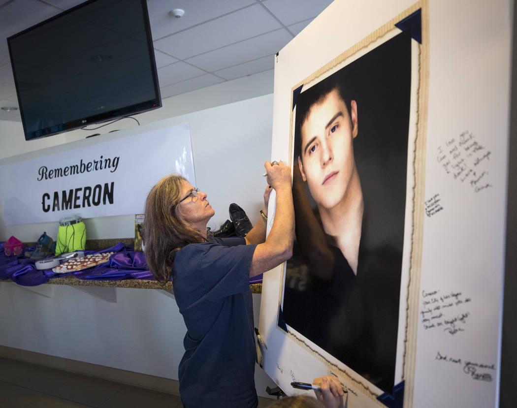 Diane Bradley, mother of Route 91 shooting victim Cameron Robinson, signs a poster of her son during a celebration of life for Robinson at Las Vegas City Hall on Thursday, Oct. 26, 2017. Richard B ...
