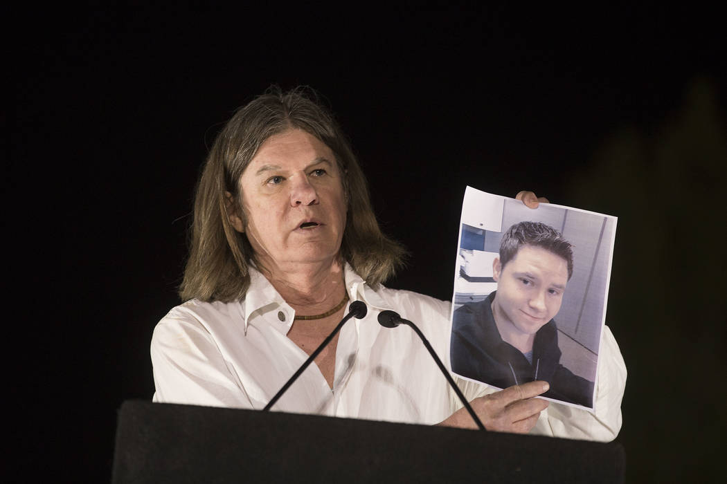 Las Vegas City Attorney Brad Jerbic holds up a sign of Las Vegas employee and Saturday shooting victim Cameron Robinson at the Community Healing Garden in Las Vegas, Friday, Oct. 6, 2017. The city ...