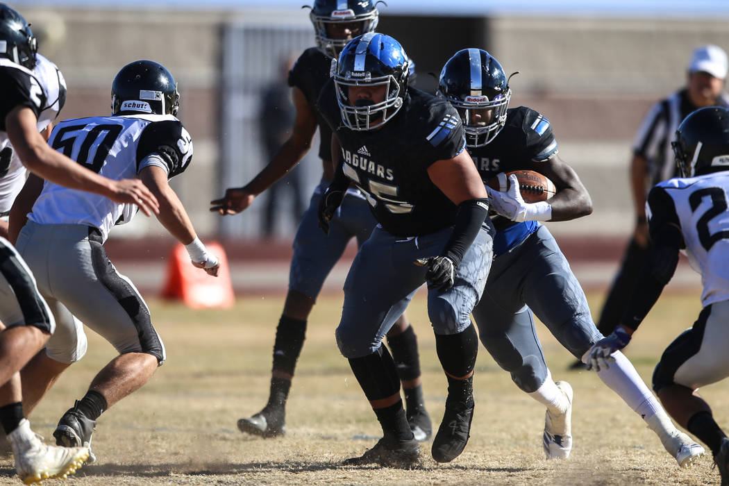 Desert Pines's Jyden King (12), right, runs the ball against Spring Creek during the first quarter of the Class 3A State football game at Desert Pines High School in Las Vegas, Saturday, Nov. 18,  ...