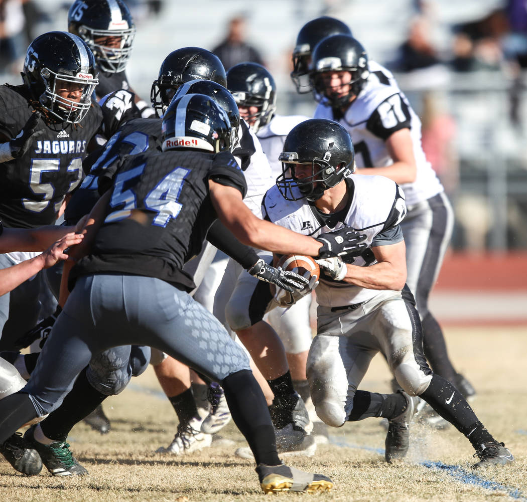 Spring Creek's Jason Painter (22), right, runs the ball against Desert Pines during the second quarter of the Class 3A State football game at Desert Pines High School in Las Vegas, Saturday, Nov.  ...