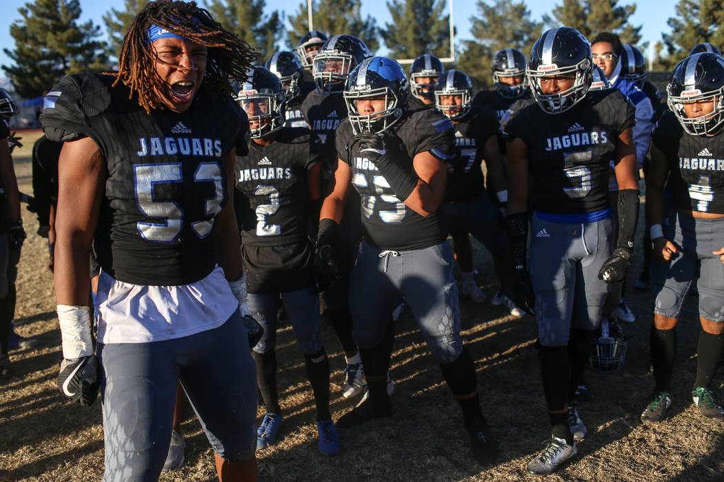 Desert Pines' Lorenzo Sheldon Brown (53), left, celebrates with teammates after defeating Spring Creek 50-28 in the end of the Class 3A State football game at Desert Pines High School in Las Vegas ...