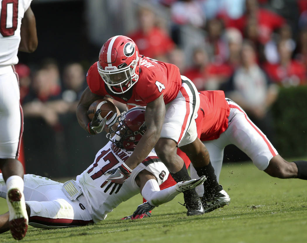 Georgia wide receiver Mecole Hardman (4) is brought down by South Carolina defensive back Javon Charleston (17) during the first half of an NCAA college football game Saturday, Nov. 4, 2017, in At ...