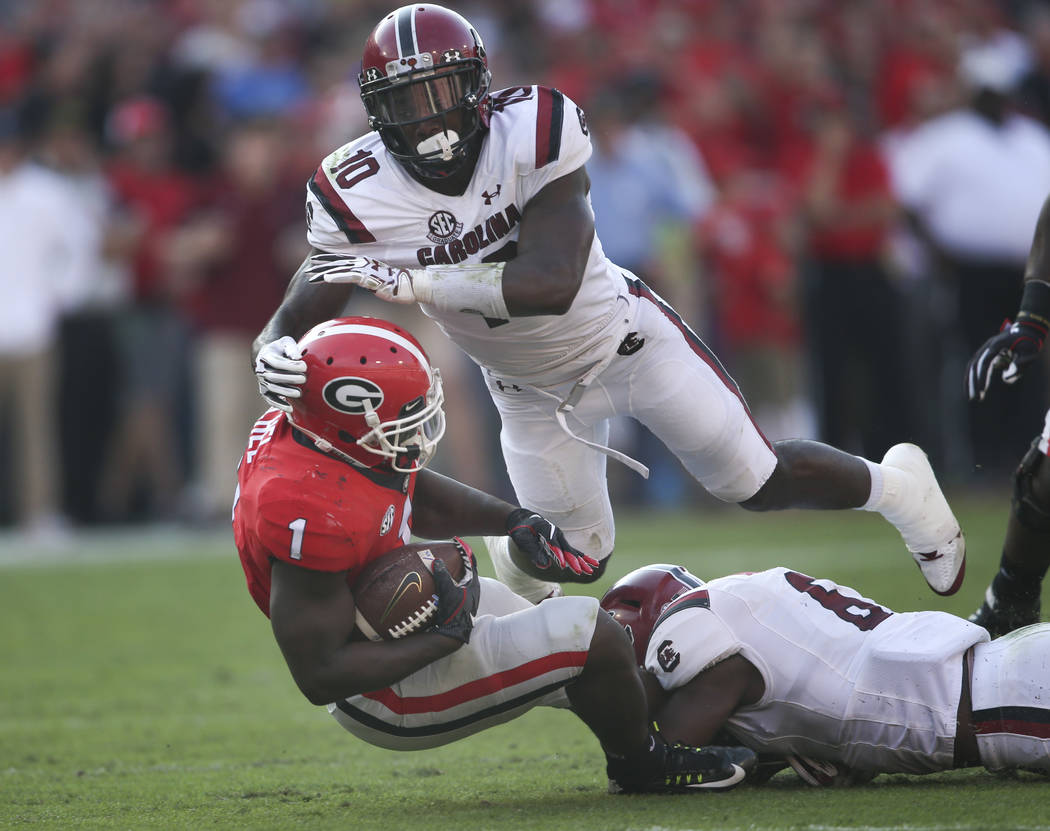Georgia running back Sony Michel (1) is tackled by South Carolina linebackers Skai Moore (10) and T.J. Brunson (6) during the first half of an NCAA college football game Saturday, Nov. 4, 2017, in ...