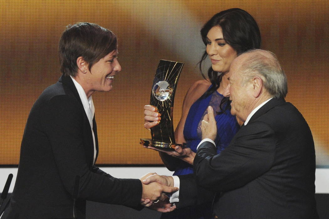 Abby Wambach, left, of the United States, is presented the FIFA Women's World Player of the Year award by Hope Solo, center, goalkeeper of the U.S. team, and FIFA President Sepp Blatter, right, du ...