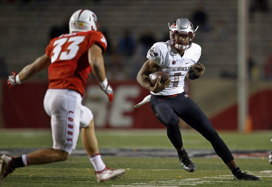 UNLV quarterback Armani Rogers, right, tries to avoid New Mexico linebacker Alex Hart (33) during the first half of an NCAA college football game in Albuquerque, N.M., Friday, Nov. 17, 2017. (AP P ...