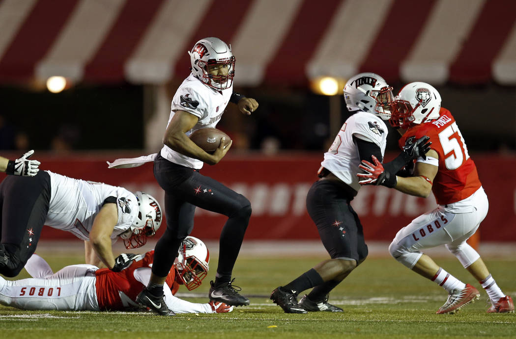 UNLV quarterback Armani Rogers, center, avoids a tackle during the first half of an NCAA college football game against New Mexico in Albuquerque, N.M., Friday, Nov. 17, 2017. (AP Photo/Andres Leig ...