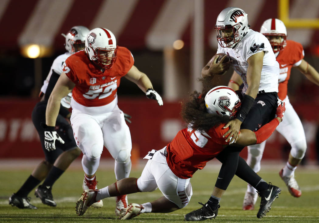 UNLV quarterback Armani Rogers, front right, is sacked by New Mexico linebacker Evahelotu Tohi (45) during the first half of an NCAA college football game in Albuquerque, N.M., Friday, Nov. 17, 20 ...