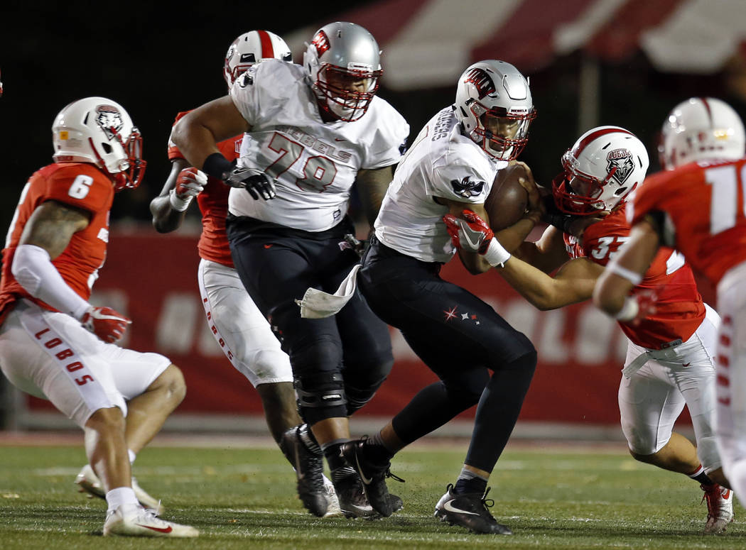 UNLV quarterback Armani Rogers (1) is slowed by New Mexico linebacker Alex Hart (33) during the first half of an NCAA college football game in Albuquerque, N.M., Friday, Nov. 17, 2017. (AP Photo/A ...