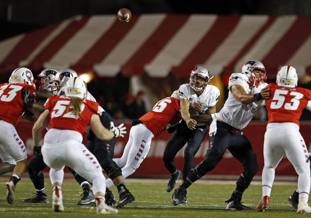 UNLV quarterback Armani Rogers, third from right, throws over New Mexico safety Kenneth Maxwell during the first half of an NCAA college football game in Albuquerque, N.M., Friday, Nov. 17, 2017.  ...