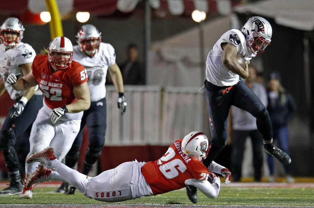 UNLV quarterback Armani Rogers, right, is tackled by New Mexico linebacker Sitiveni Tamaivena (26) during the second half of an NCAA college football game in Albuquerque, N.M., Friday, Nov. 17, 20 ...